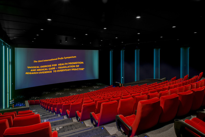 "The picture of the auditorium of Finnkino Scala with the text reflected on its screen: ""International 23rd Puijo Symposium - ""Physical Exercise for Health Promotion and Medical Care - Translation of Research Evidence to Everyday Practice""."